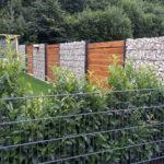 """Ein trister Garten mit kurzem Rasen, fehlenden Blüten, giftigem Kirsch-Lorbeer im Vordergrund, Gabionen-Wand. Im Hintergrund sieht man einen mit Kunststoffplane """"geschmückten"""" Zaun, auf die die Pflanzen nur noch aufgedruckt sind.  Pflegeleicht - aber dieser Garten hat dem Klimawandel nichts entgegen zu setzen."""